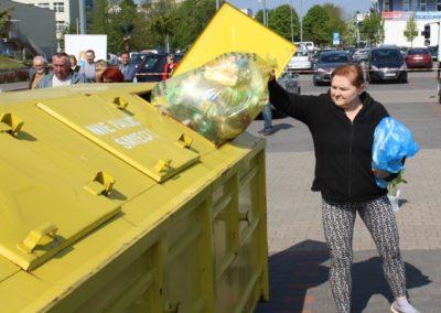 kobieta wrzucająca plastiki do żółtego kontenera