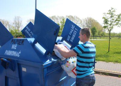 mężczyzna wrzuca papier do niebieskiego kontenera