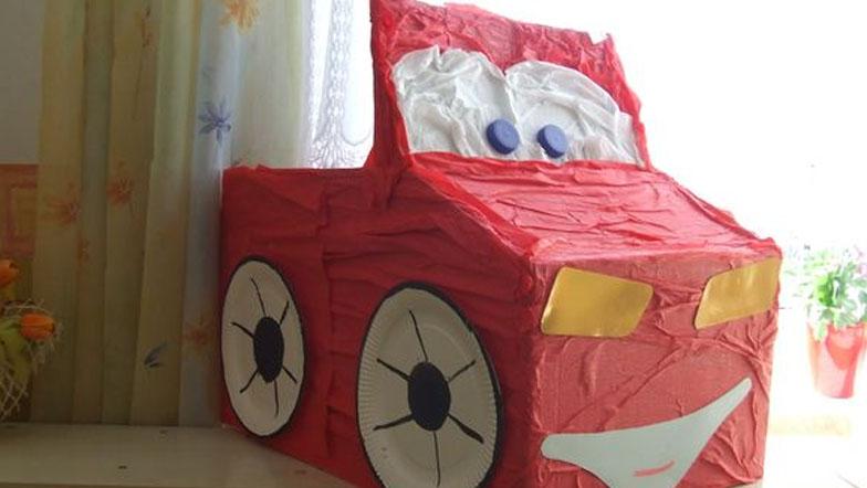czerwony samochód zbudowany z odpadów