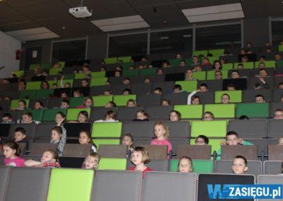 dzieciaki siedzące na auli