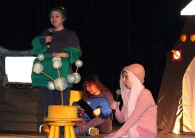 aktorzy ubrani na kolorowo odgrywają rolę na scenie