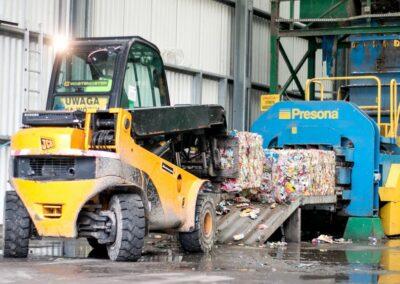 ładowarka układająca odpady uformowane w kostkę na prasie
